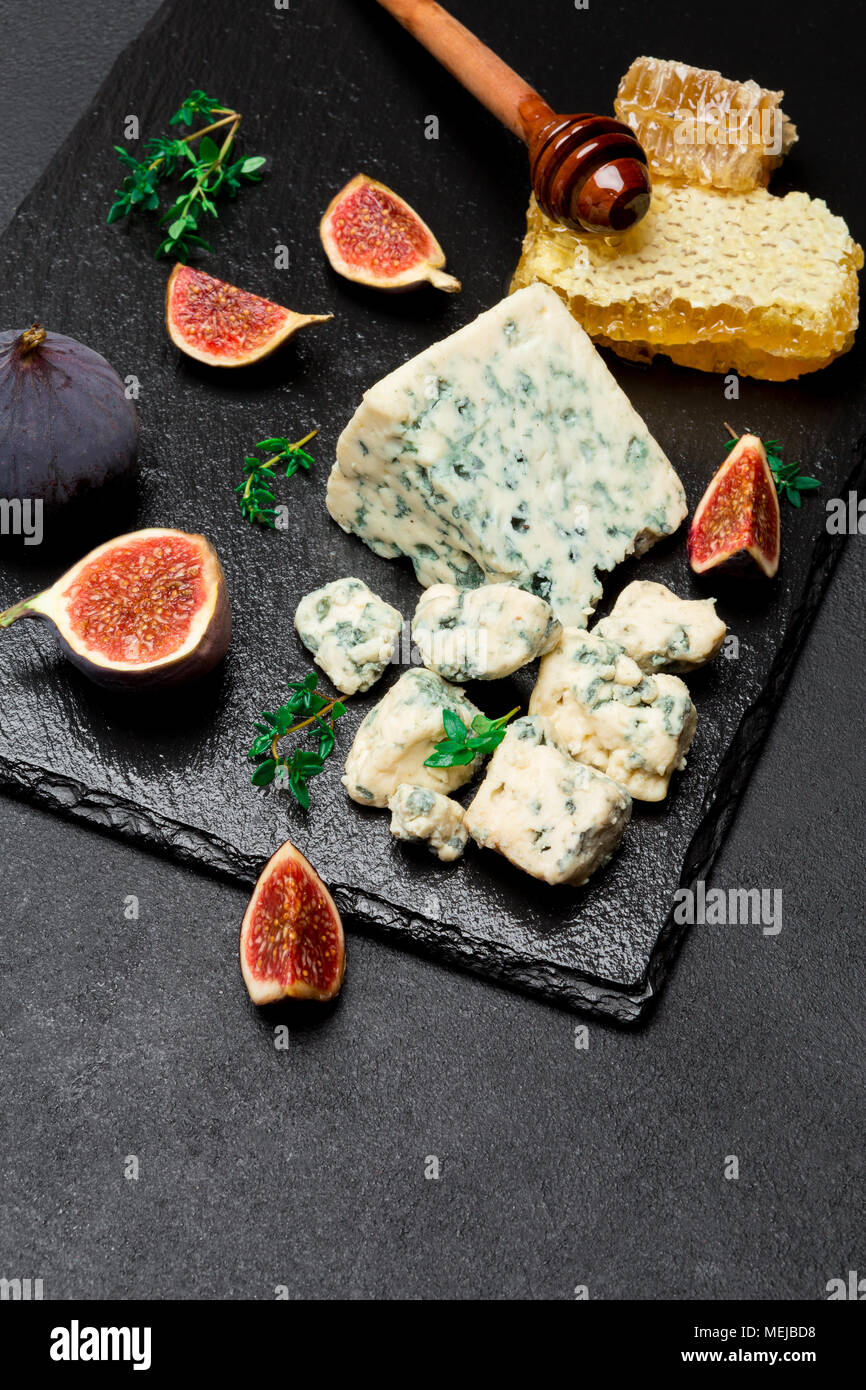 Roquefort cheese and cut a slice on stone serving board - Stock Image