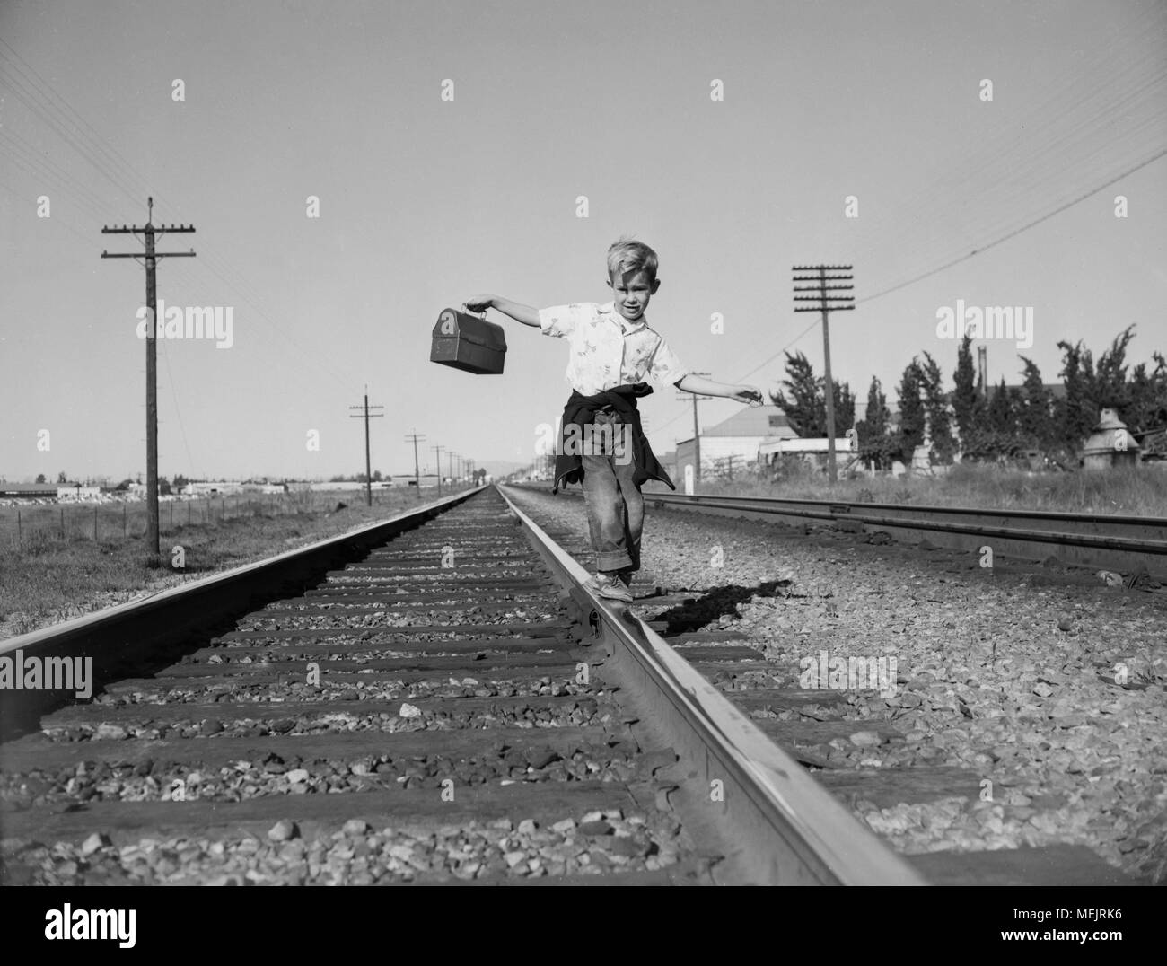 A young boy, in a dangerous habit, walks home from school balancing on railroad tracks, ca. 1964. - Stock Image