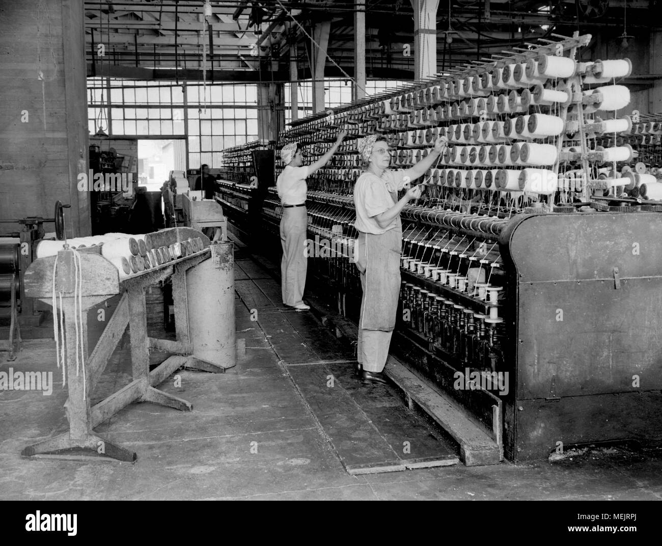 A worker watches an early industrial plastic manufacturing process in a California factory, ca. 1946. - Stock Image