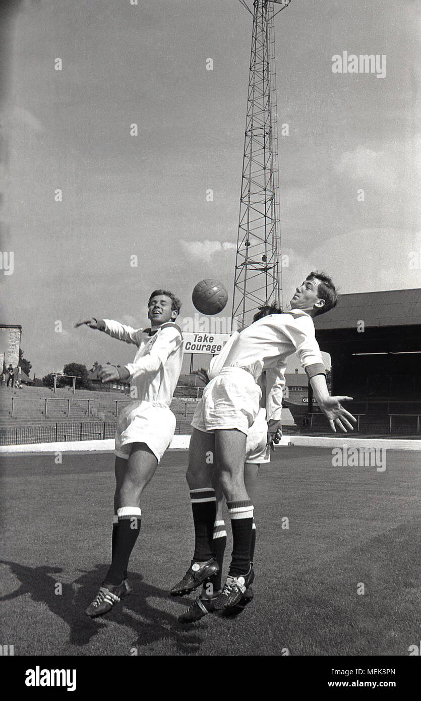 1964, Charlton Athletic FC, historical picture showing Charlton players at the Valley leaping with the ball wearing their new football kit. Between 1964 and 1966 the Charlton players wore a smart all white kit with red shoulders and the hand and sowrd badge first appeared on the shirt. Stock Photo