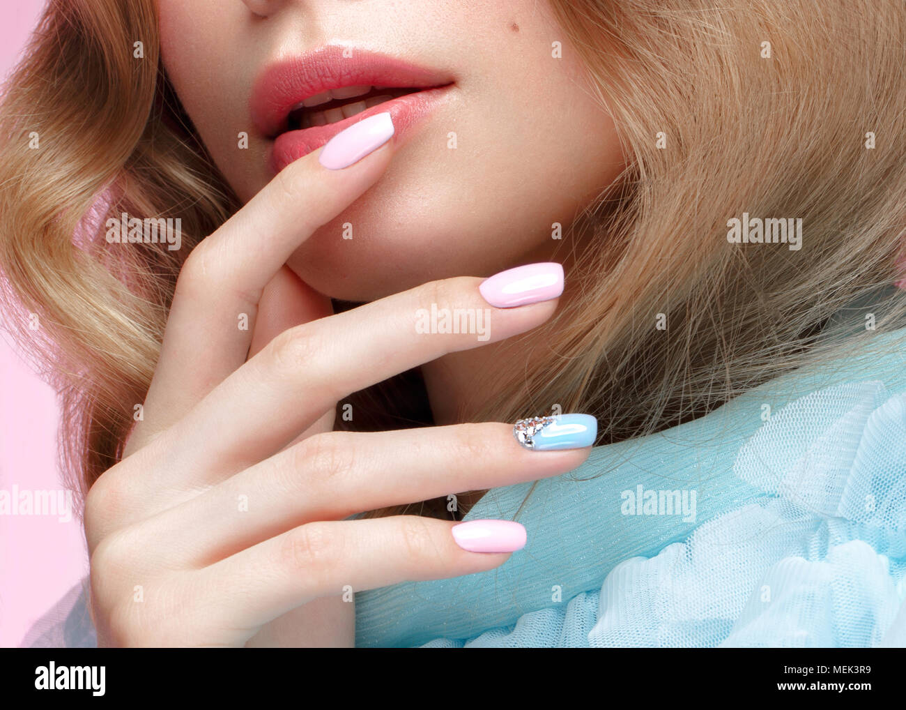 Beautiful girl with light make-up and gentle manicure in blue clothes. Beauty face. Design nails. - Stock Image