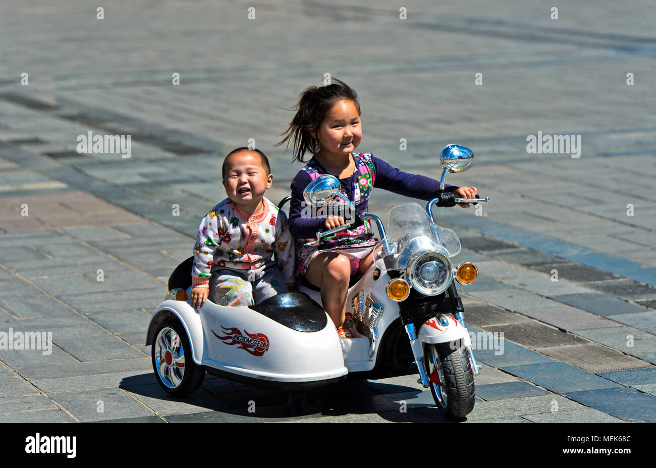 6 to 8-year old girl riding an electric toy motor-bike with her brother on Sukhbaatar  Square, Ulaanbaatar, Mongolia - Stock Image