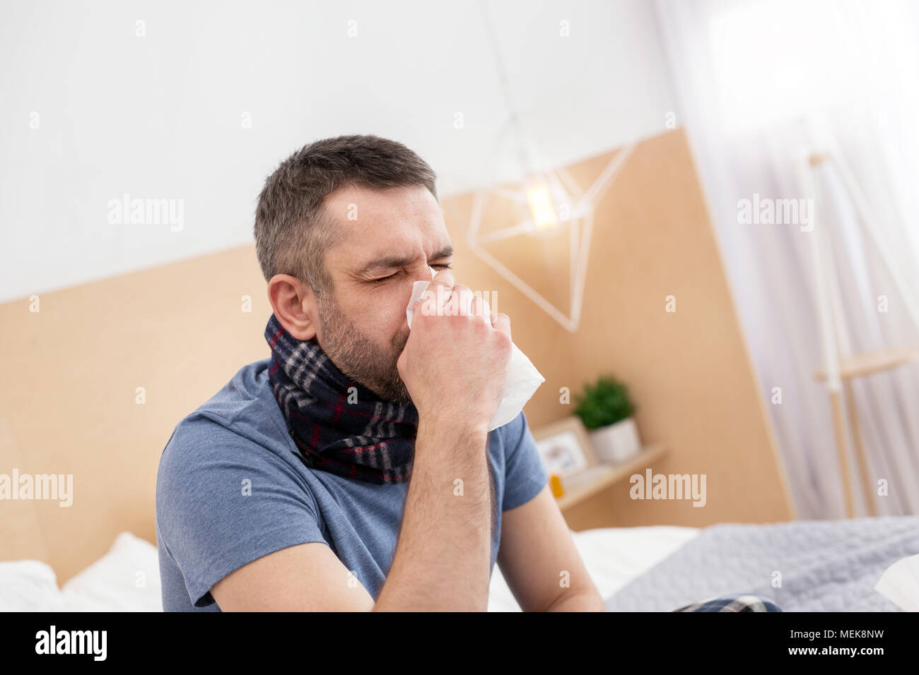 Sick man blowing his nose - Stock Image