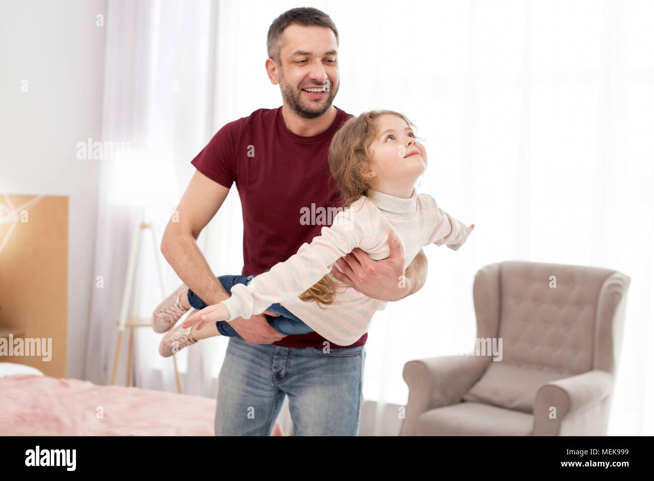 Cheerful father having fun with his daughter - Stock Image