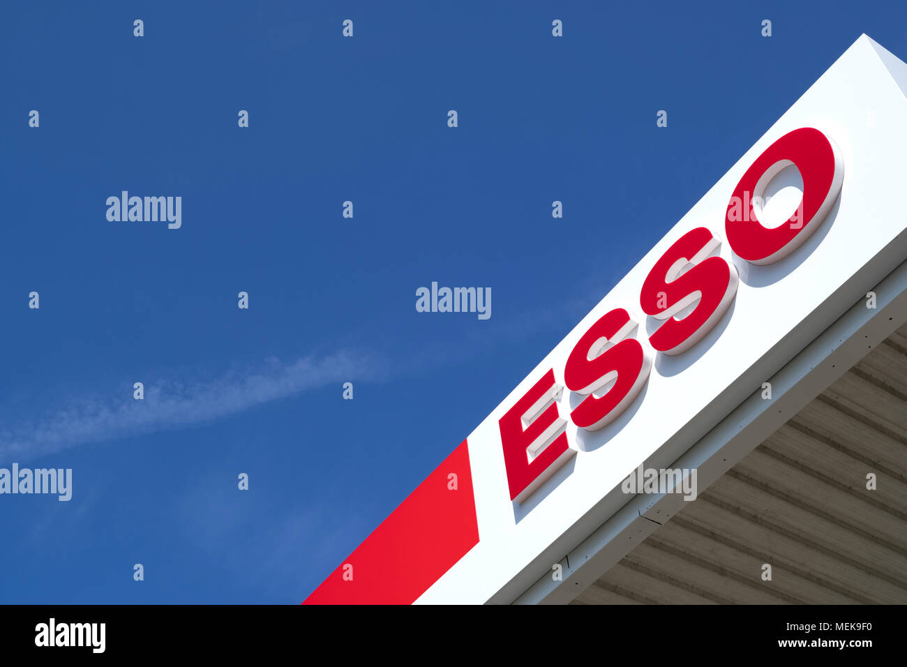 Esso sign at gas station against blue sky. Esso is ExxonMobil's primary gasoline brand worldwide. - Stock Image