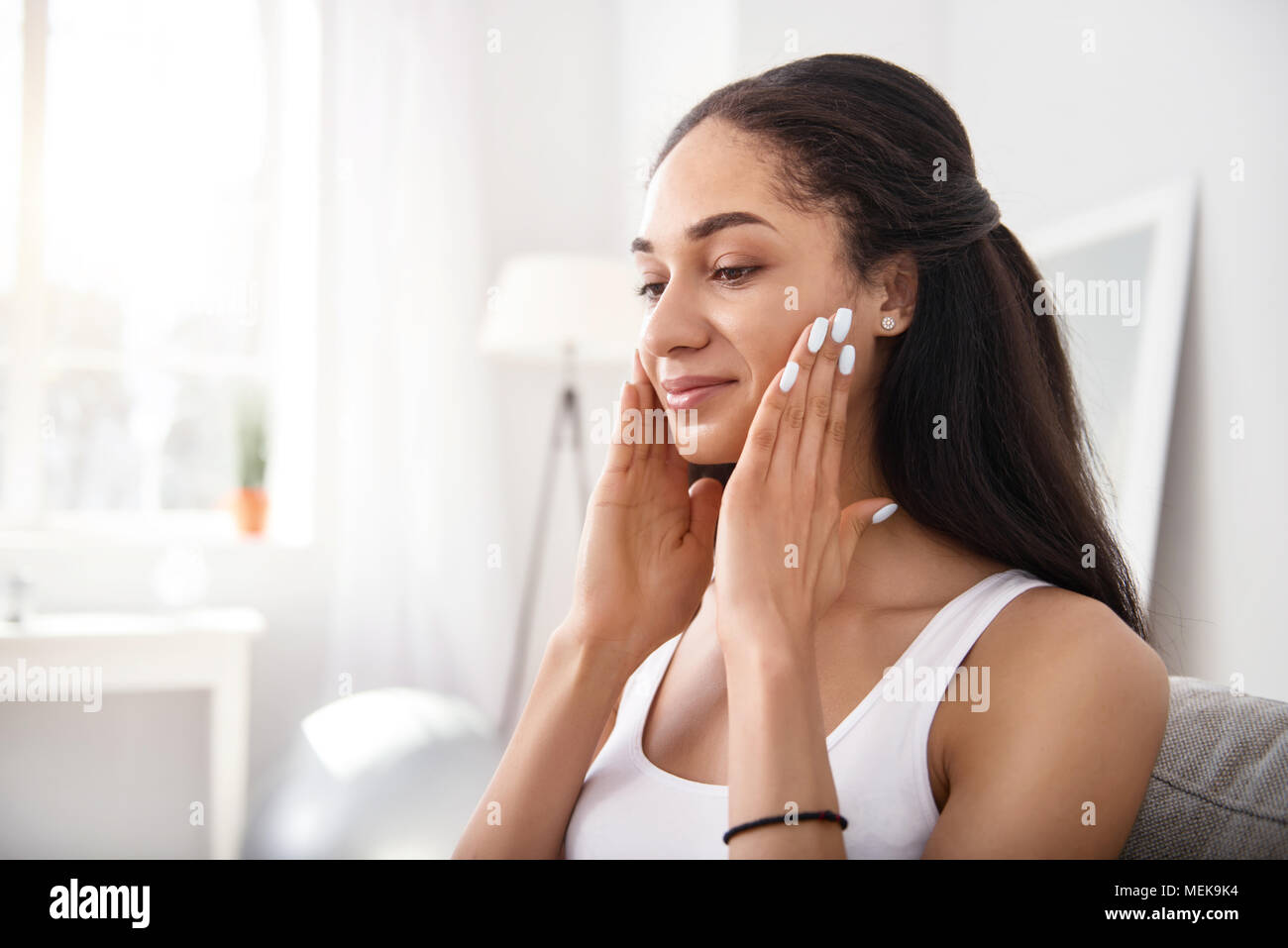 Pretty young woman doing facial massage - Stock Image