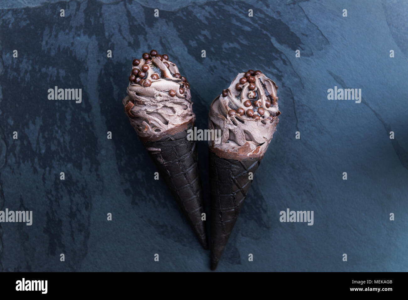 Double Chocolate Ice Creams with Black Waffle Cones on Dark Background - Stock Image