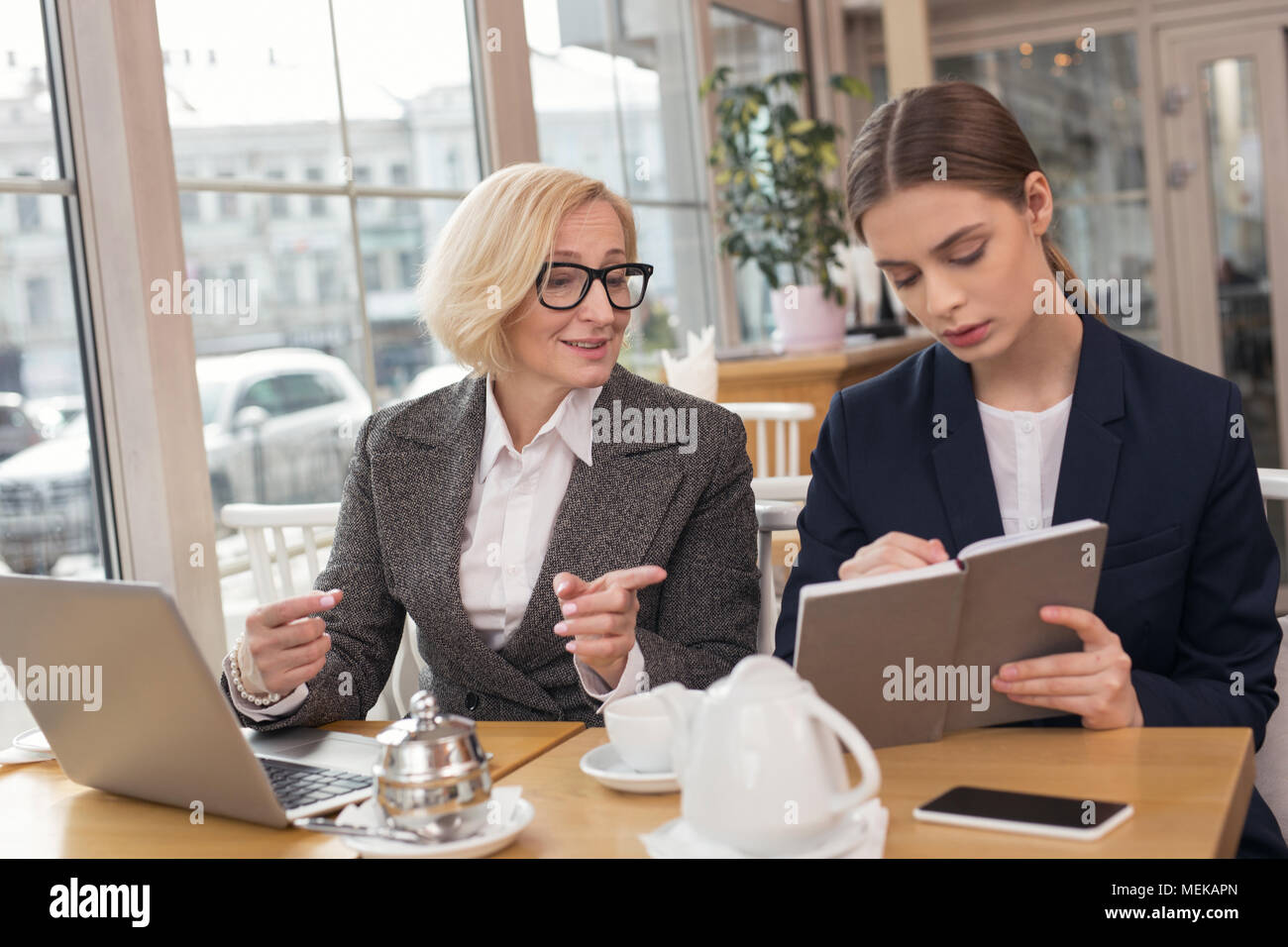 Inspired woman discussing business with her employer - Stock Image