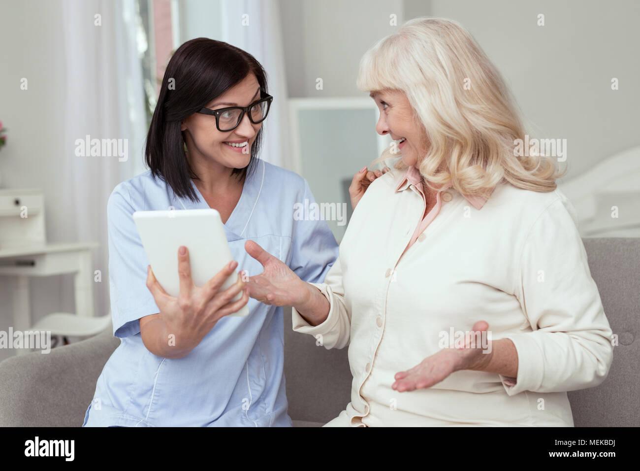 Joyful elder woman learning tablet usage - Stock Image