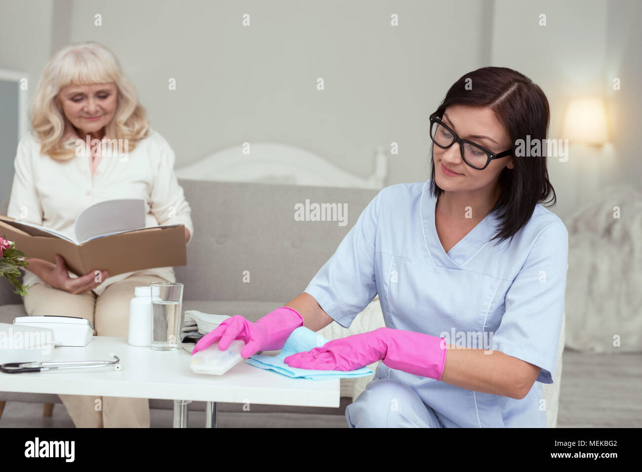 Pensive female caregiver cleaning house - Stock Image
