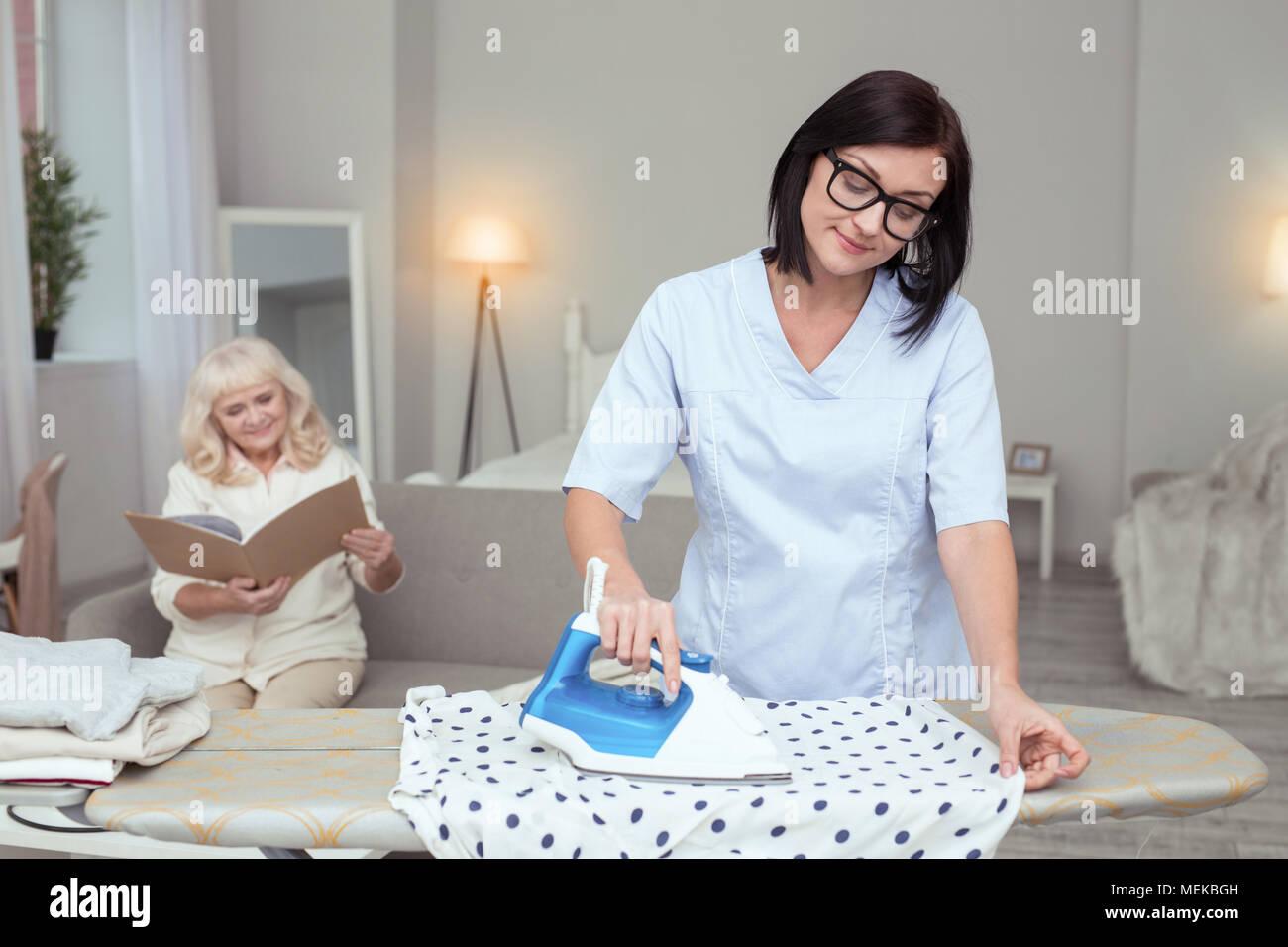 Reflective female caregiver helping with ironing - Stock Image