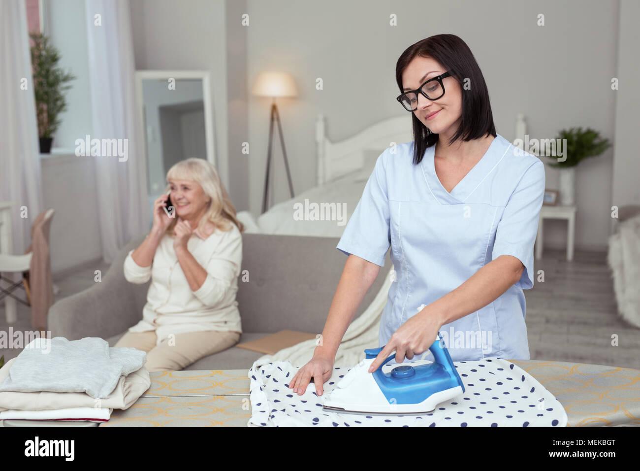 Attractive female caregiver finishing ironing - Stock Image