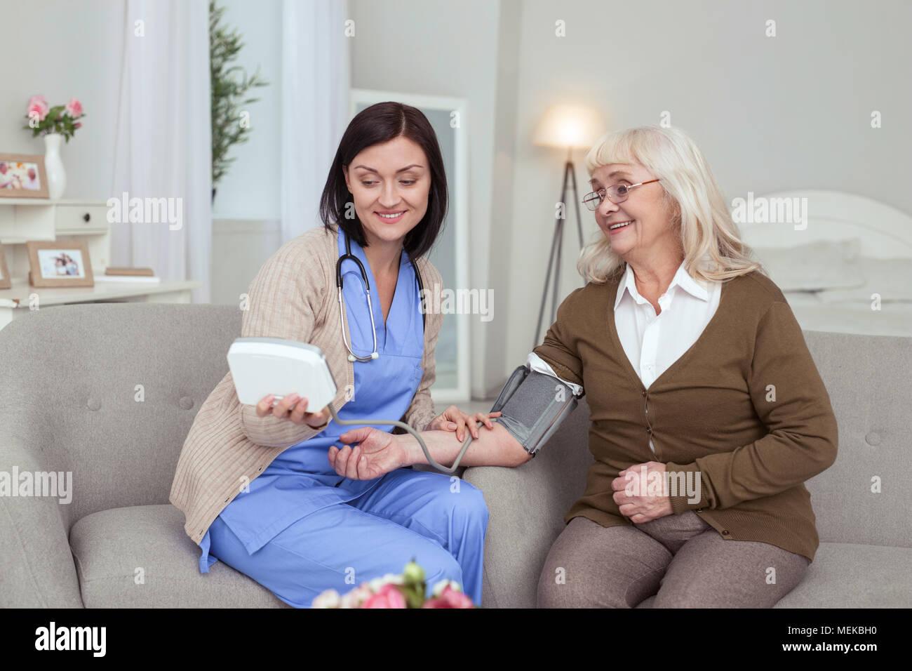 Gay female caregiver measuring blood pressure - Stock Image