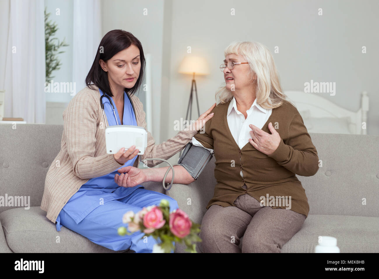 Uneasy elder woman complaining on blood pressure - Stock Image