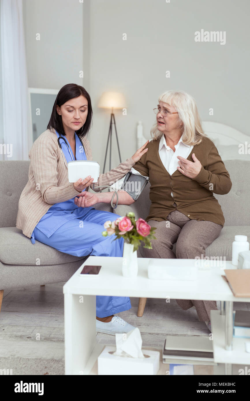 Pretty female caregiver watching blood pressure changes - Stock Image