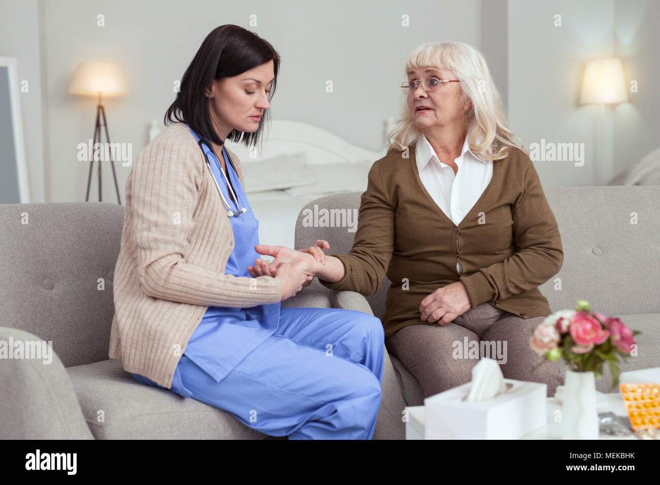 Focused female caregiver monitoring pulse - Stock Image