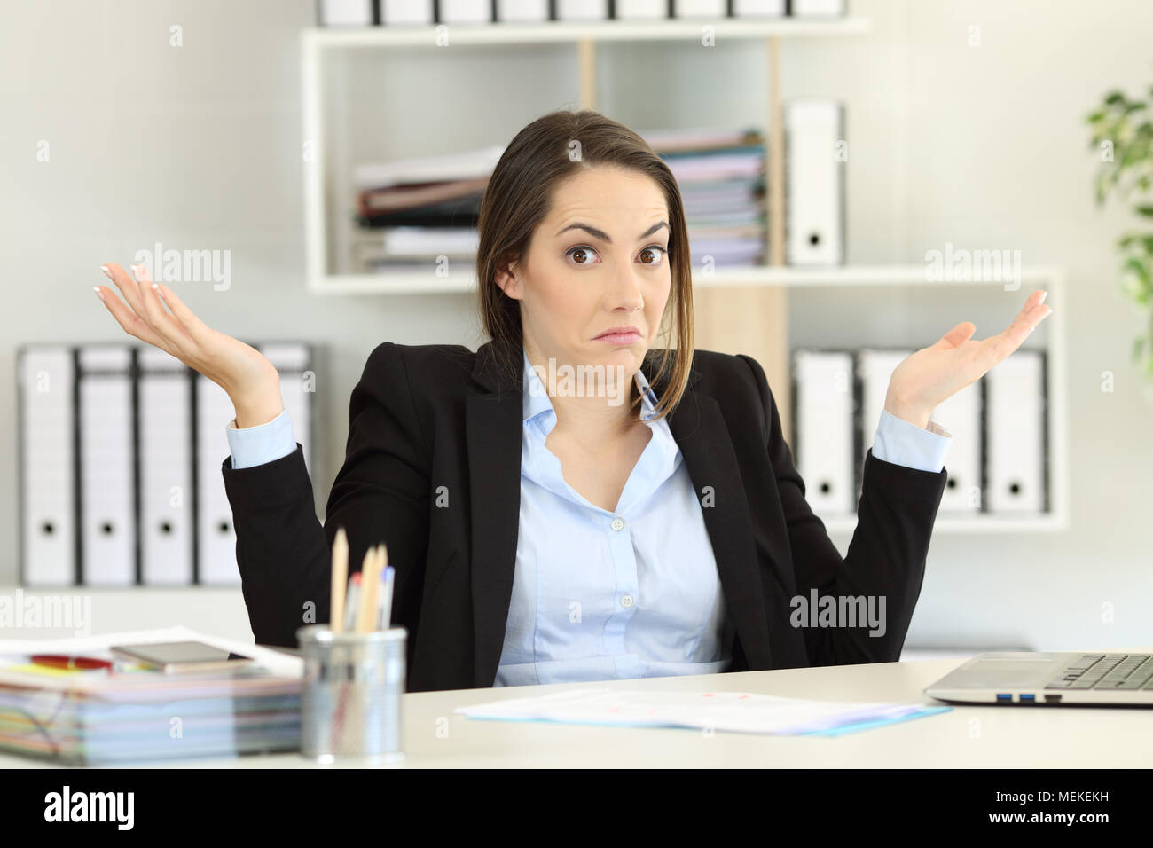 Front view portrait of a confused businesswoman shrugging shoulders looking at camera at office - Stock Image