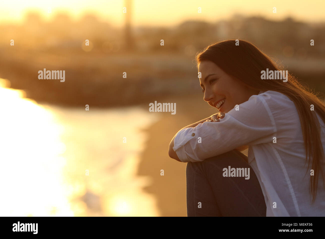 Happy girl contemplating landscape sitting outdoors at sunset - Stock Image