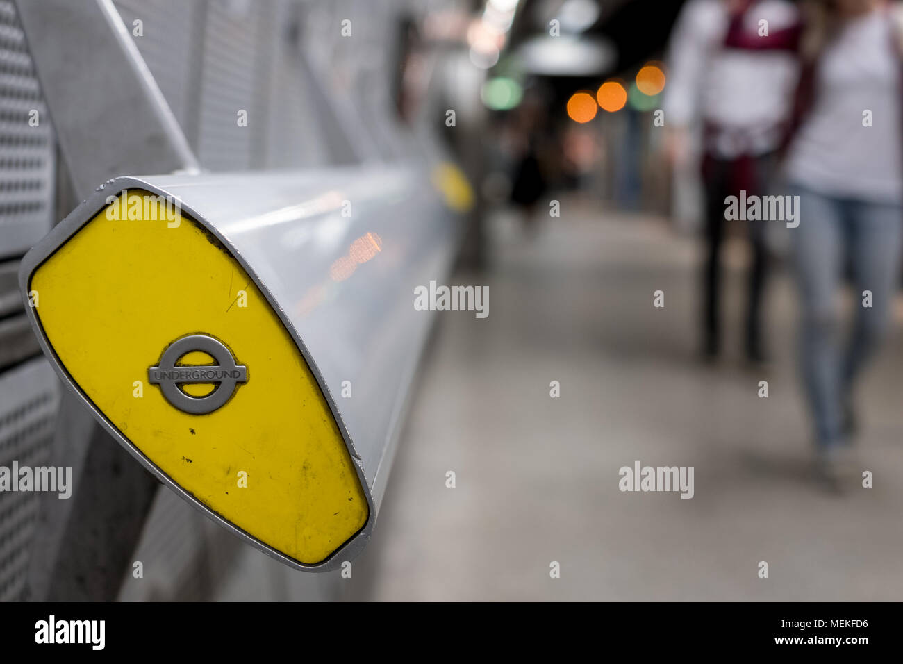 In foreground, end of handrail at Westminster underground station, London showing TFL roundel. In background blurred commuters walking along platform, - Stock Image