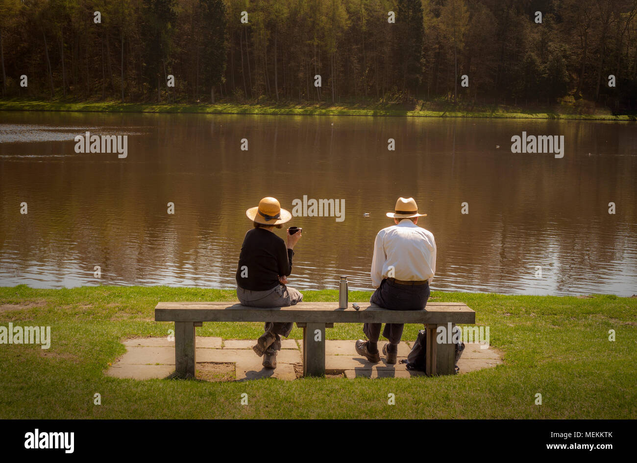 Old couple sat on bench in front of lake enjoying a flask of tea or coffee in sunshine - Stock Image