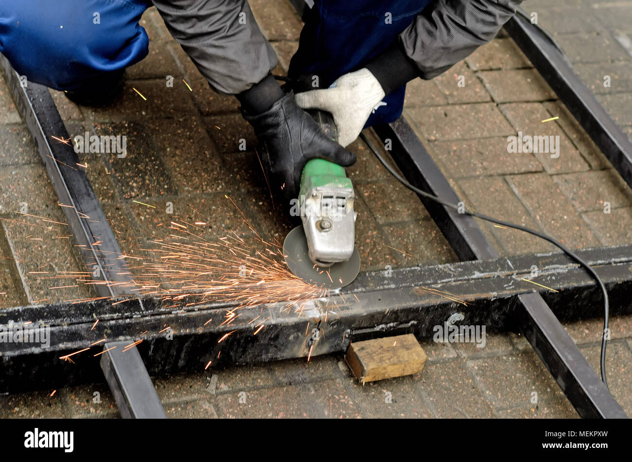 worker in gloves cleans the angle grinder metal construction. - Stock Image