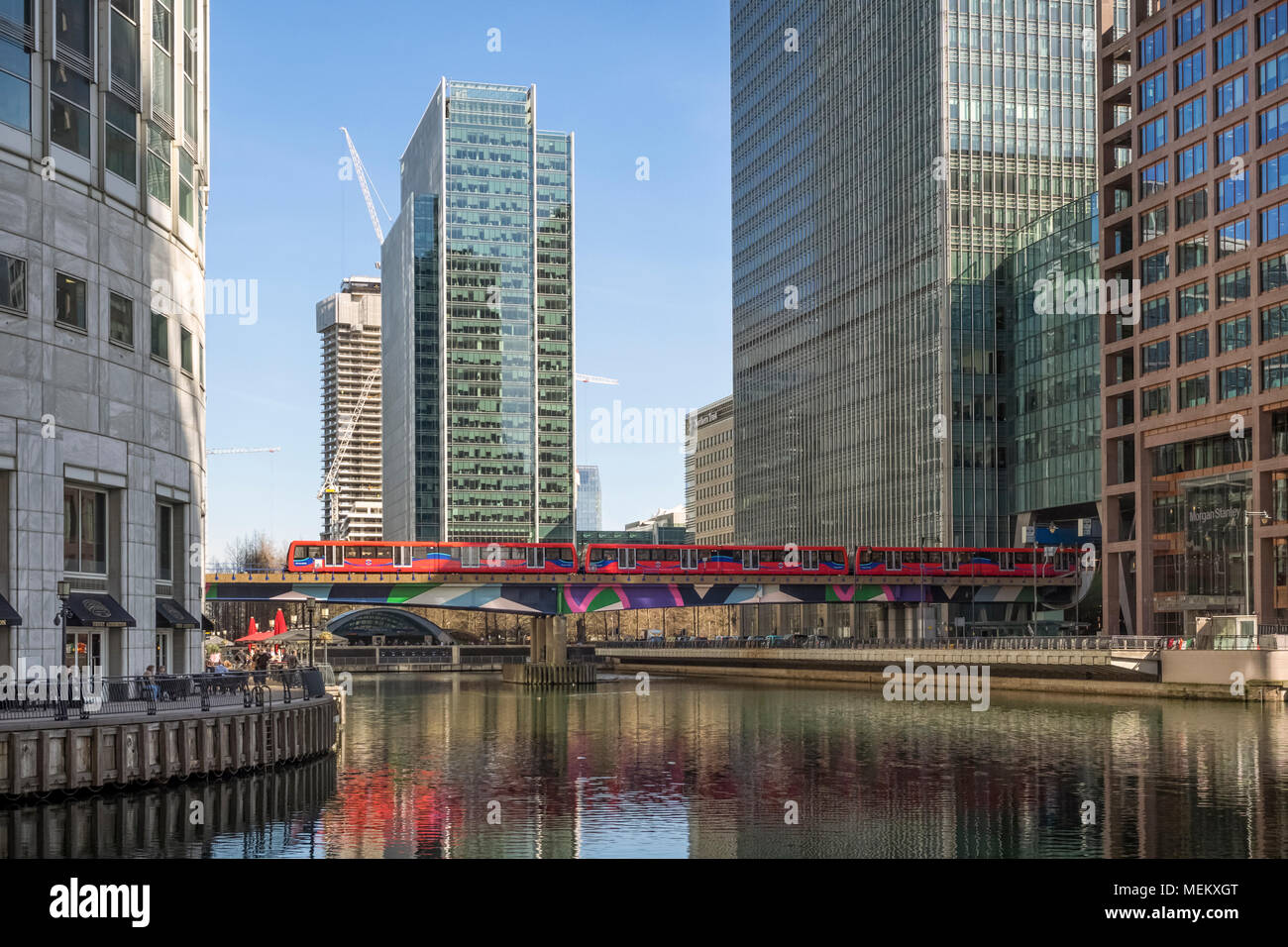 CANARY WHARF, DOCKLANDS, LONDON:  Docklands Light Railway (DLR) train passing offices - Stock Image