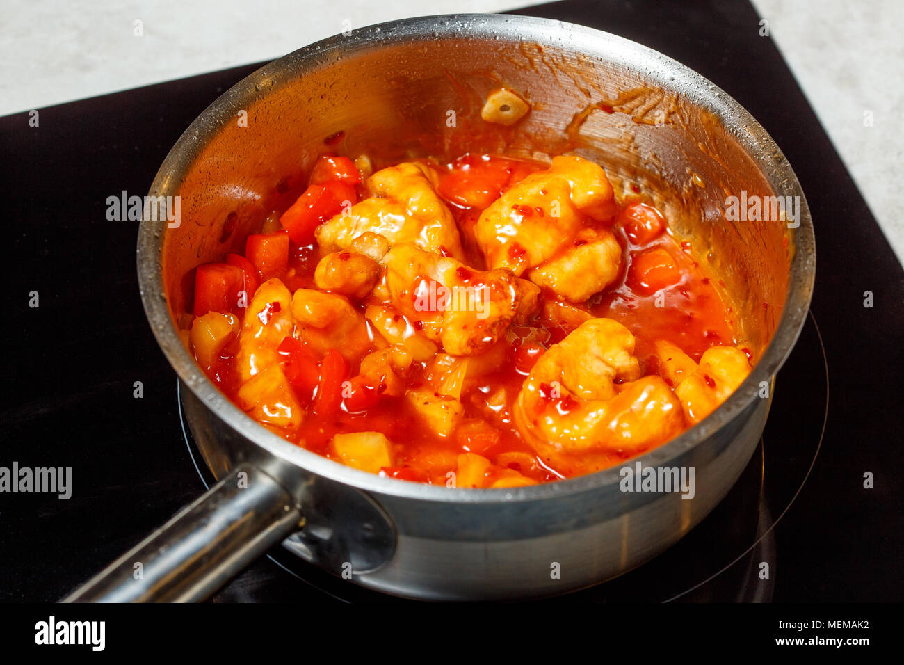 Cooking process of chinese sweet and sour fried chicken food, close up - Stock Image