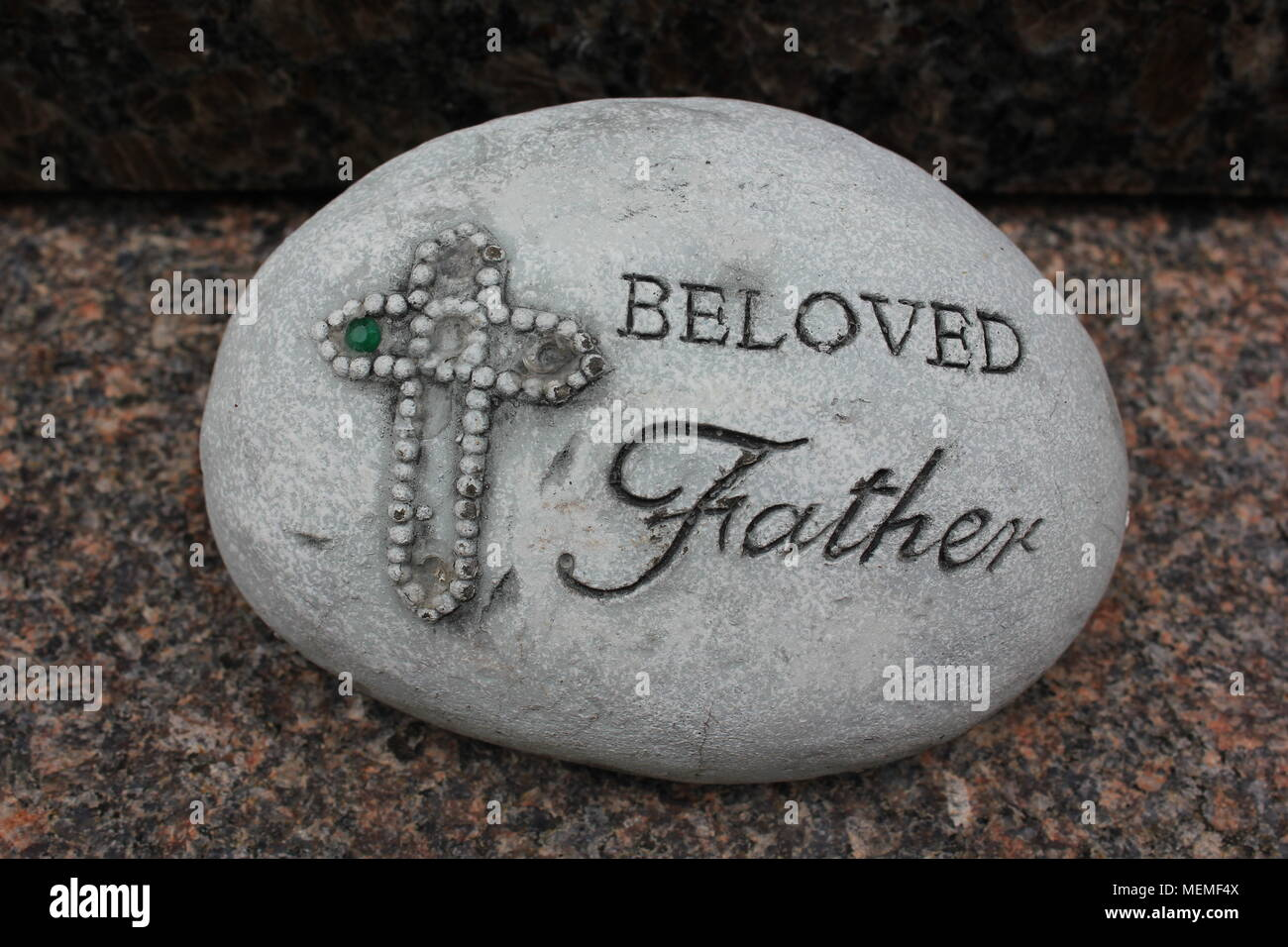 Memorial rock that states 'Beloved Father' next to a decorated cross. - Stock Image