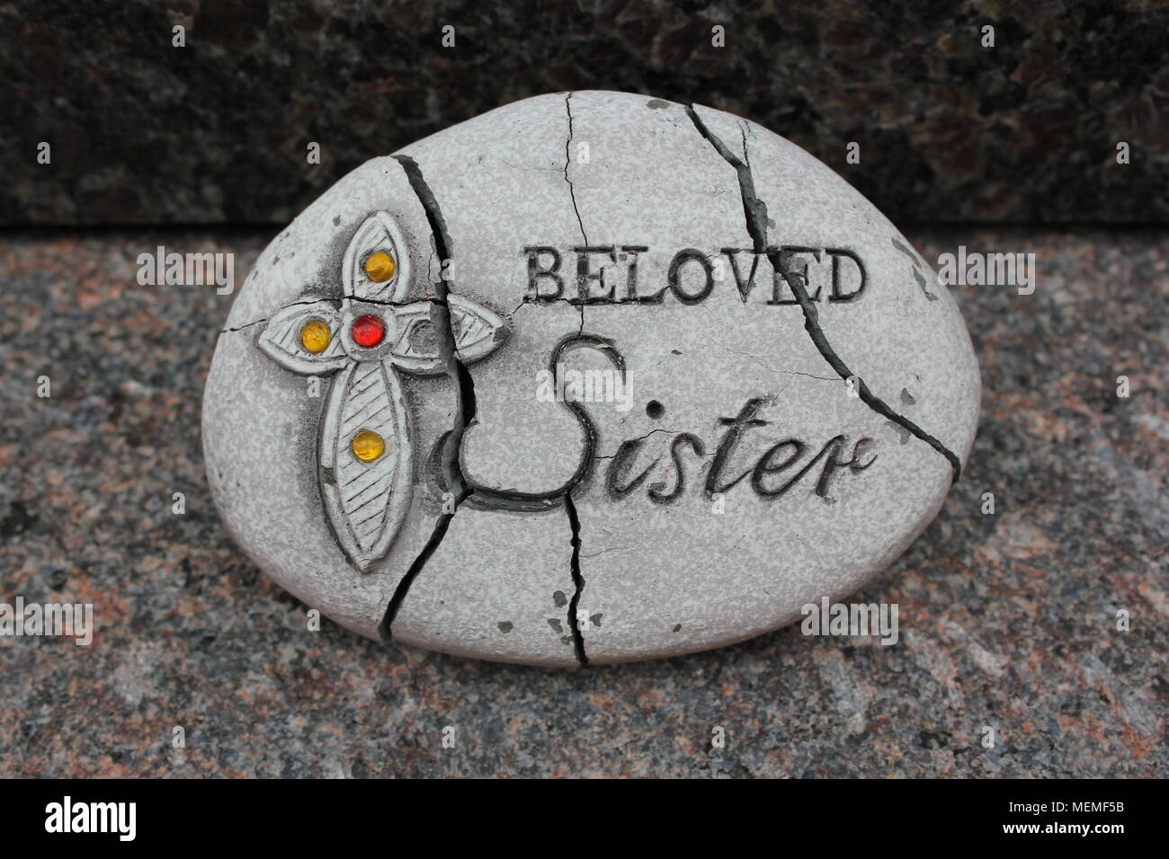 Memorial rock that states 'Beloved Sister' next to a decorated cross. - Stock Image