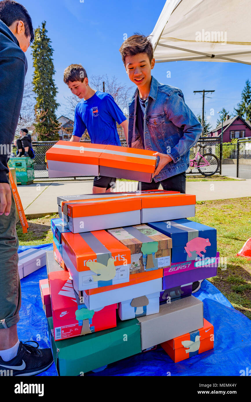 Teen playing Environmental Jenga game, species are all interconnected,, Earth Day event, Vancouver, British Columbia, Canada. - Stock Image