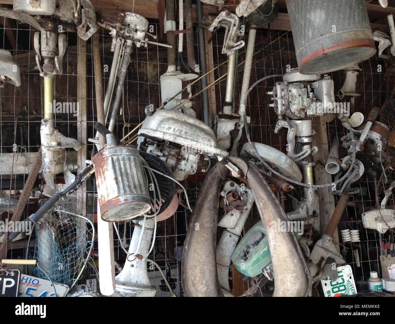 Old, vintage outboard motors hanging from the ceiling of a back country fishing camp in Florida - Stock Image