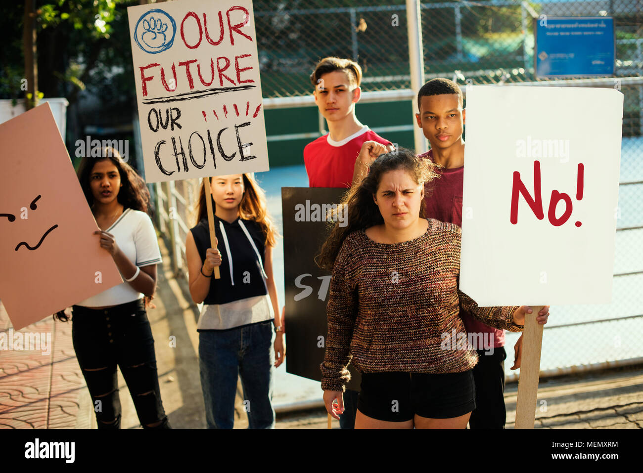 Group of teenagers protesting demonstration holding posters antiwar justice peace concept - Stock Image