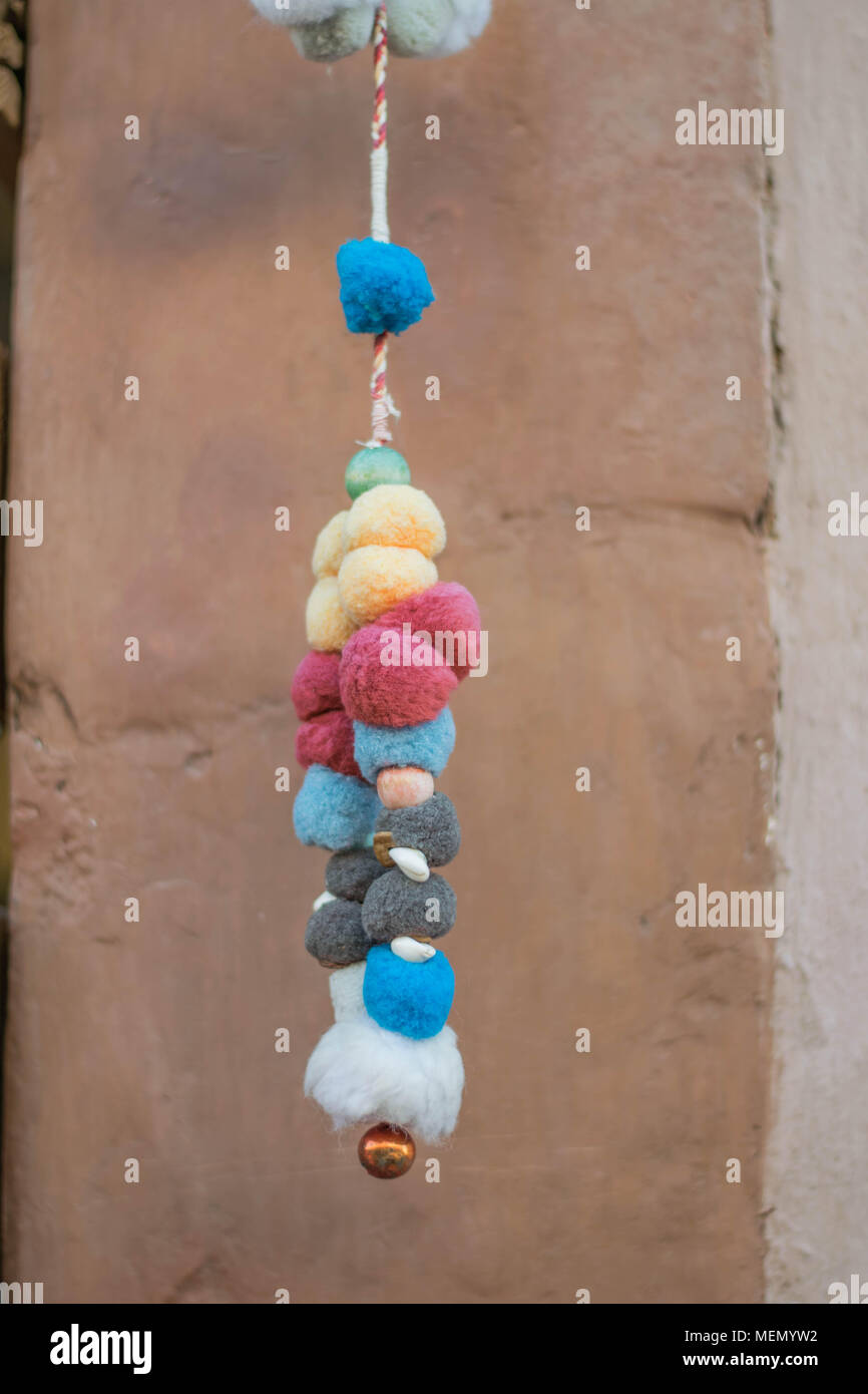 Colorful Fuzzy Balls-festive multi-colored fuzzy balls, threaded on thin rope and hanging, with a stone wall background, in Mexico - Stock Image