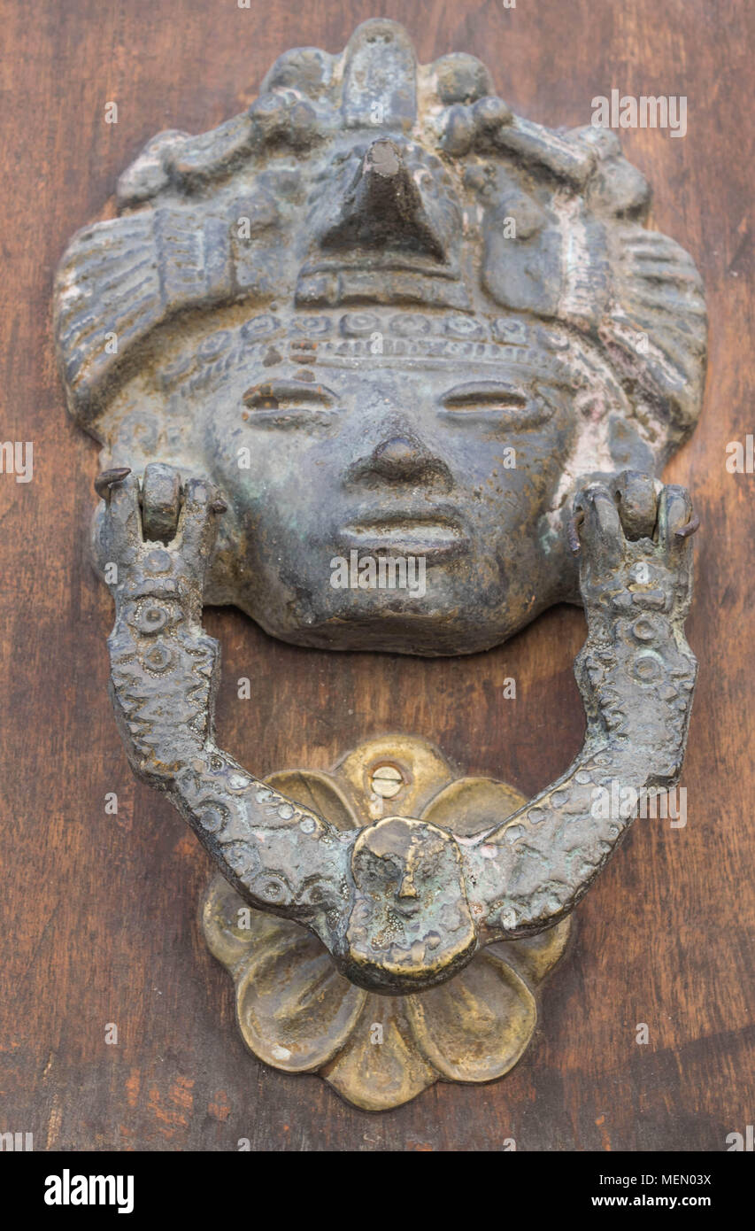 Isolated Shot Of An Antique Door Knocker, With Detail Resembling A Mayan  Face And Head Piece, A Decorative Handle And Floral Shaped Base, In Mexico