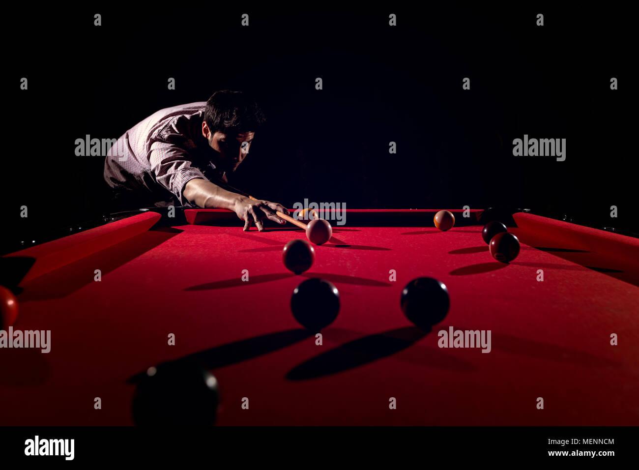 A man with a beard plays a big billiard. - Stock Image