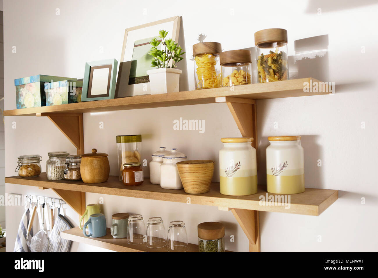 wooden shelf carry a lot of stuff on the wall of kitchen Stock Photo