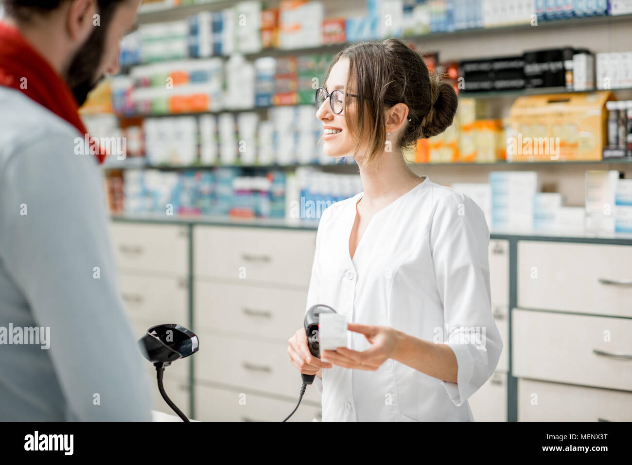 Pharmacist selling medications in the pharmacy store - Stock Image