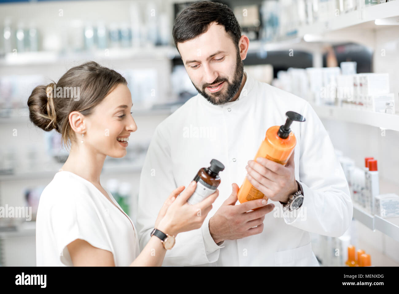 Pharmacist with client in the pharmacy store - Stock Image