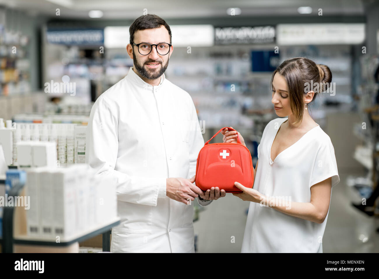 Pharmacist with client and first aid kit in the pharmacy - Stock Image