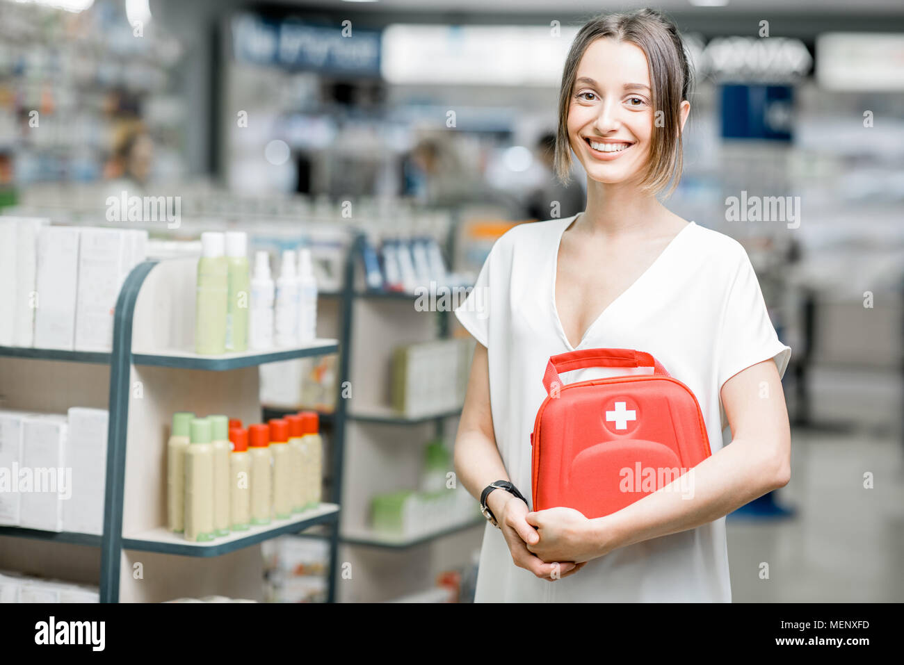 Woman with first aid kit in the pharmacy - Stock Image