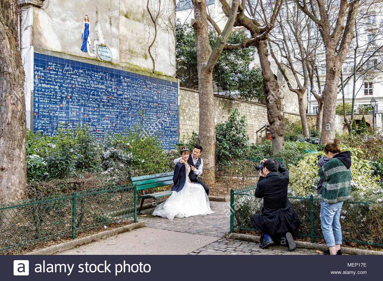 Chinese Bride and Groom pose for pictures in front of Le Mur des je taime, Wall Of I Love You ,in Jehan Rictus Square , Abbesses, Montmartre, Paris - Stock Image