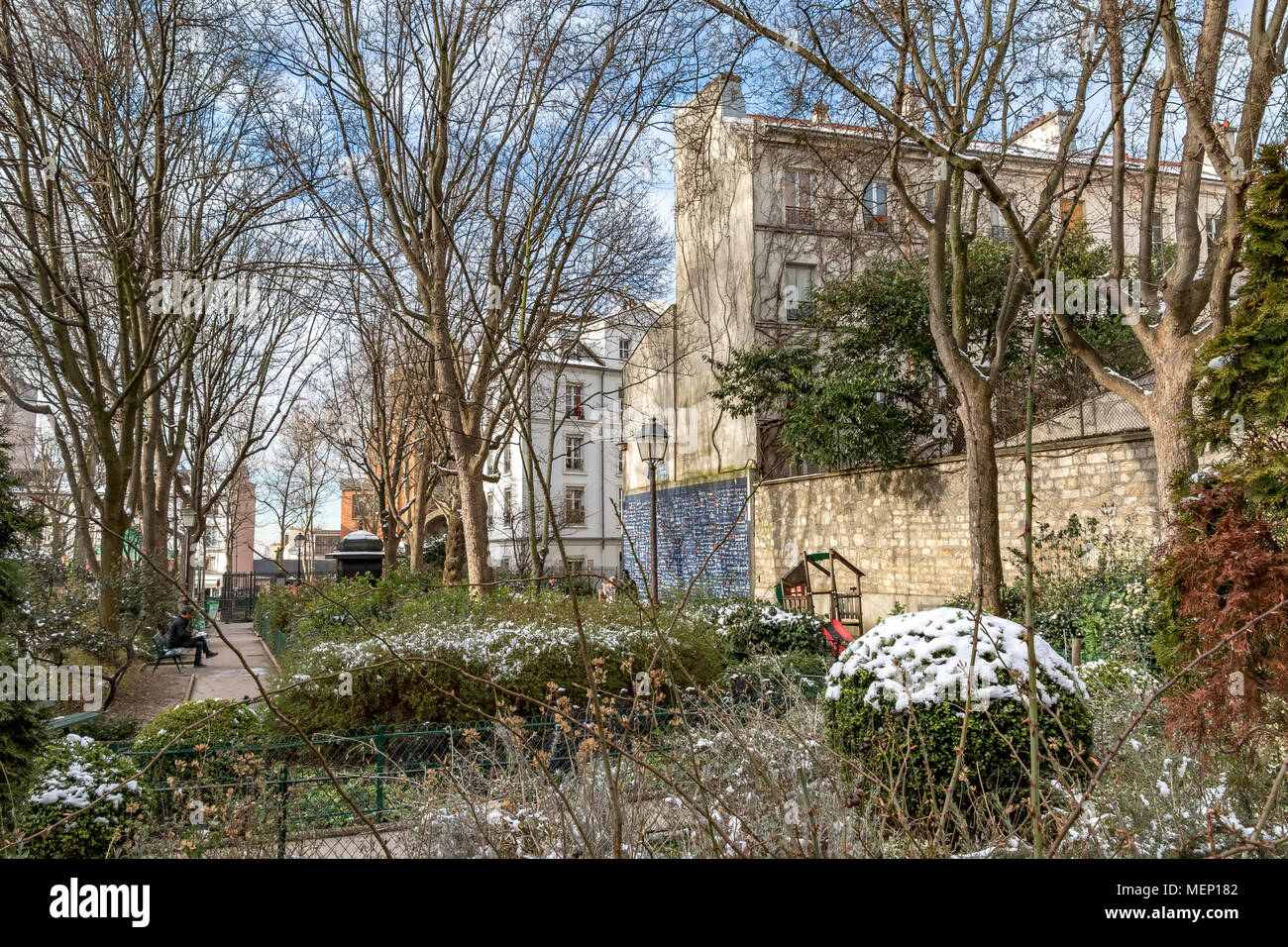 A lone man sits on a bemch inJehan Rictus Square with the Le Mur des je taime in winter, with snow on the shrubs, Abbesses, Montmartre, Paris, France - Stock Image