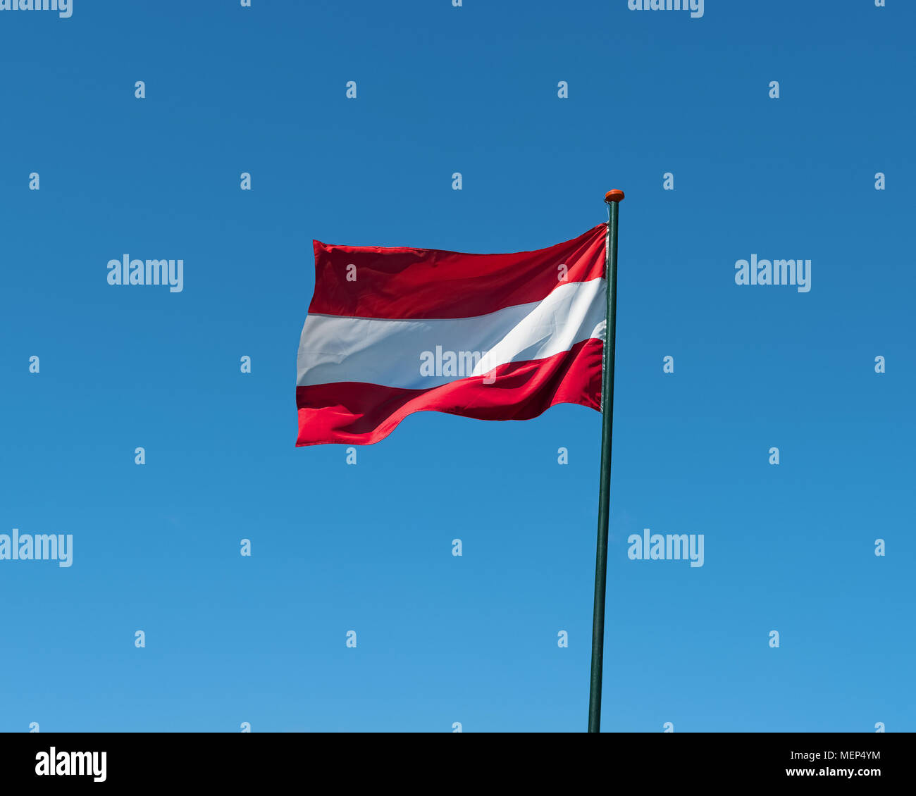 Flag of Austria on flagpole waving in the wind. Austrian national official flag on blue sky background. Patriotic symbol, banner - Stock Image
