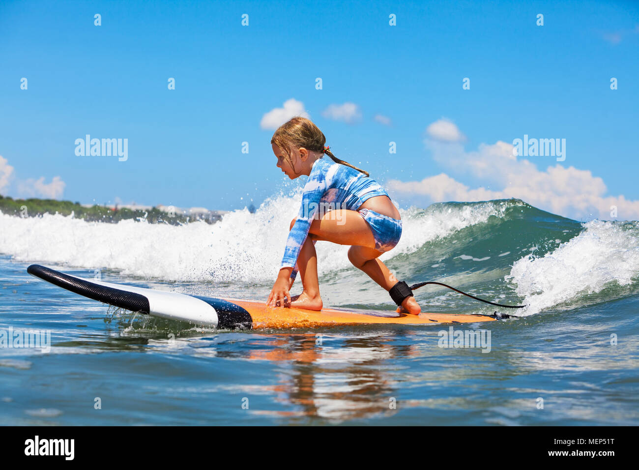 Happy baby girl. young surfer ride on surfboard with fun on sea waves. Active family lifestyle, kids outdoor water sport lessons and swimming activity - Stock Image