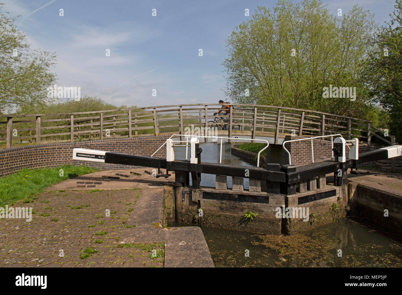 Watermead Country Park in Leicestershire, England. A cyclist crosses a bridge across a canal with lock gates in the foreground. - Stock Image