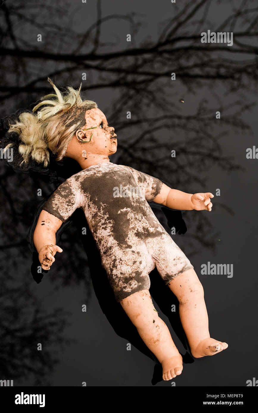 Overhead view of dirty plastic doll lying in a shallow puddle. - Stock Image