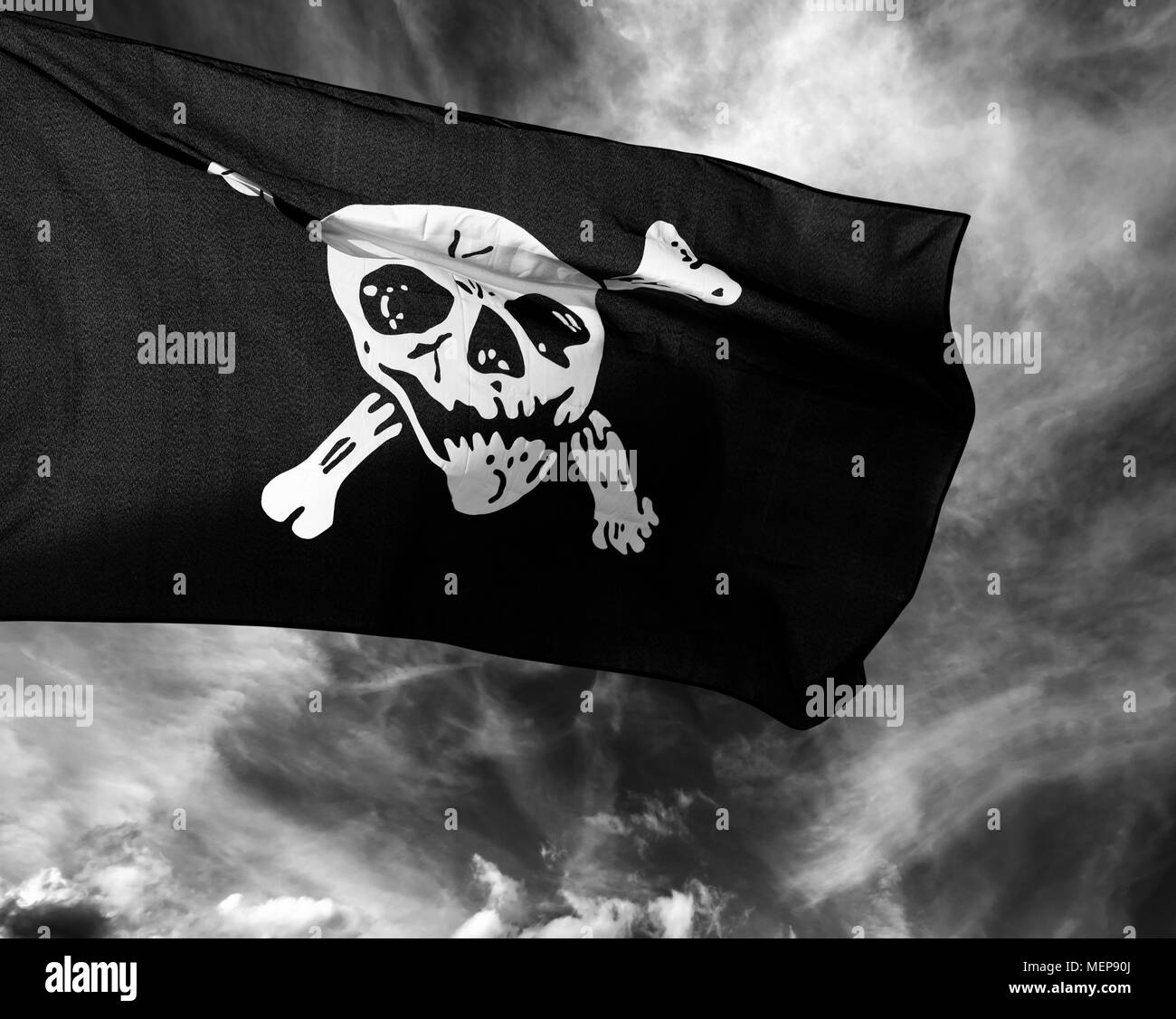 Black and white Jolly Roger (pirate flag) against storm clouds - Stock Image