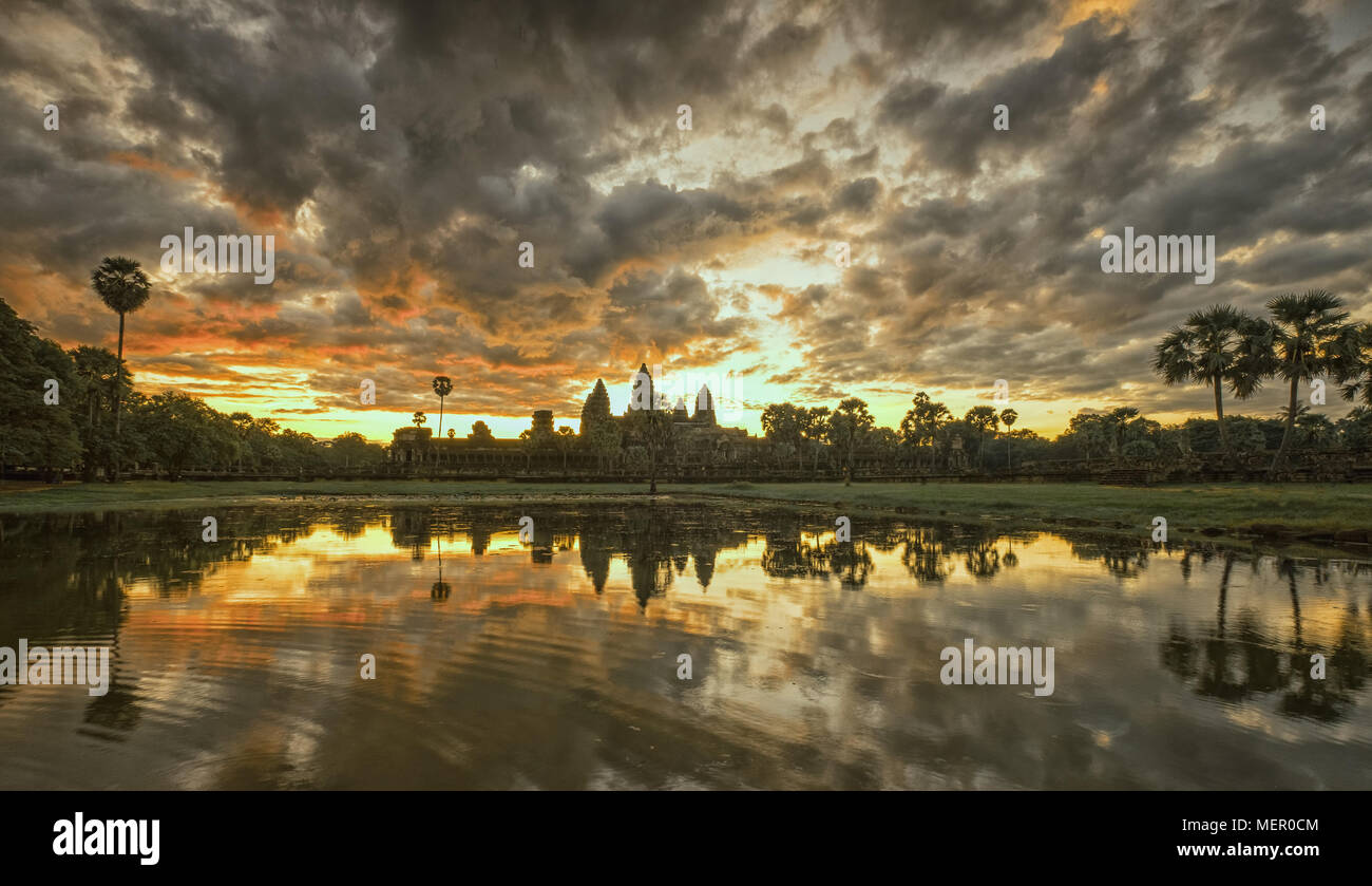 Cambodia ancient Temple Complex Angkor Wat at sunrise with dramatic clouds over the towers and reflection in the pond. Famous travel destination. - Stock Image