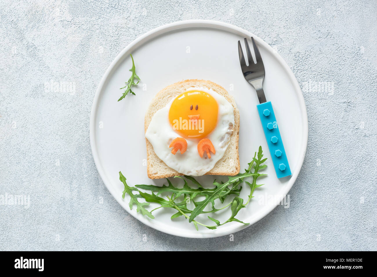 Food art chicken sandwich for kids. Cute egg sandwich shaped as chicken on white plate. Top view - Stock Image