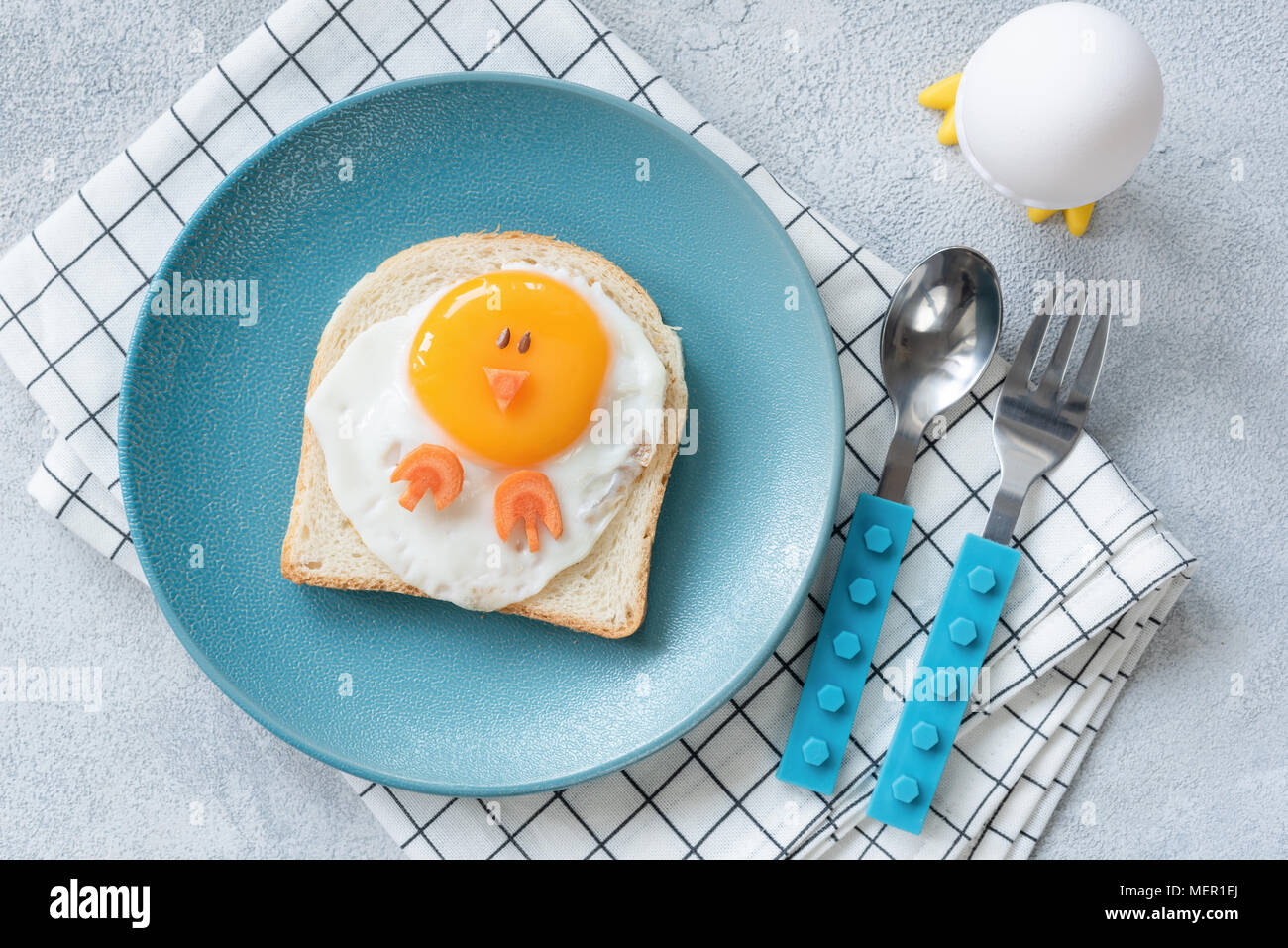 Funny egg toast for kids on blue plate, top view. Chicken shaped sandwich, food art. - Stock Image
